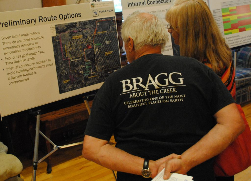 Residents take a peak at a board outlining options for a West Bragg Creek emergency egress. Photo: Enrique Massot