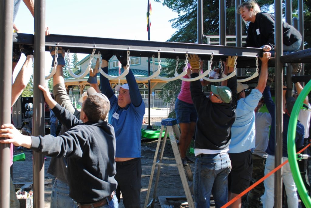 Volunteers install another piece of the new Bragg Creek playground. Photo: Enrique Massot